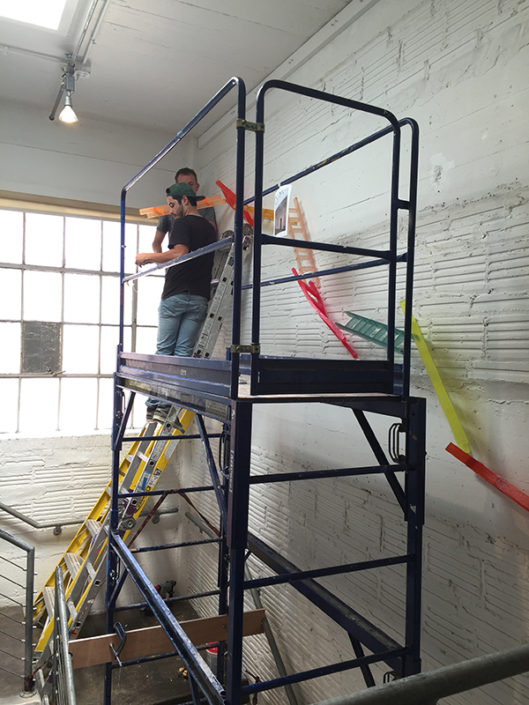 Up and Out, 2016, found objects and steel cable, installation in process at Artpace stairwell, San Antonio, Texas